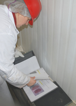 A Truebridge evaluator checking a binder filled with specification sheets.